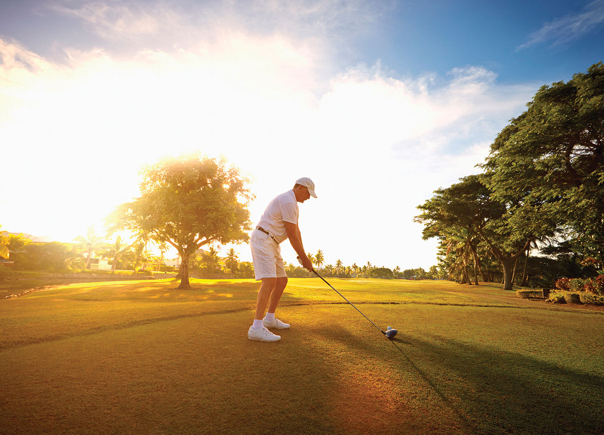 Man playing Golf in tropical surroundings with brigh blue sky.
